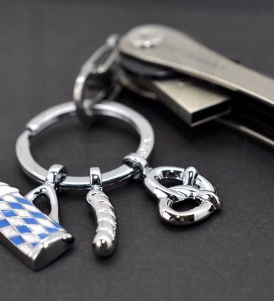 Der Oktoberfest Anhänger kommt mit drei Anhängern. - Oktoberfest-Schlüsselanhänger mit 3 typisch bayrischen Anhängern Weißwurst Brezel und Bierglas Metallguss/Emaille glänzend verchromt blau/weiß
