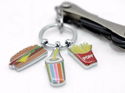 Schlüsselanhänger I love Burgers - Der Schlüsselanhänger für alle Fastfood Fans kommt mit 3 Anhängern: Burger, Trinkbecher, Pommes Frites Tüte, Produziert ist der I love Buger aus Metallguss/Emaille und er ist glänzend verchromt