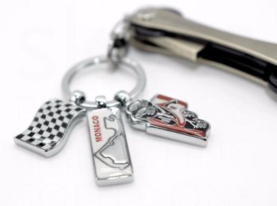 Schlüsselanhänger Racing - Einem Rennauto, einer Zielflagge und dem Formel 1 Kurs Monaco. Hergestellt ist er aus Metallguss/Emaille, glänzend verchromt