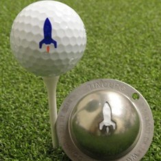 Tin Cup - Launch It - Der Tin Cup ist eine Ball Schablone aus Edelstahl mit dem Design einer aufsteigenden Rakete. Mit einem feinen und wasserfesten Stift laesst sich dann das Design auf den Golf Ball malen.