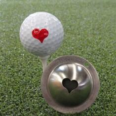 Tin Cup - Kiss me - Der Tin Cup ist eine Ball Schablone aus Edelstahl mit dem Design eines Herzens. Mit einem feinen und wasserfesten Stift laesst sich dann das Design auf den Golf Ball malen.