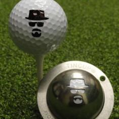 Tin Cup - Incognito - Der Tin Cup ist eine Ball Schablone aus Edelstahl mit dem Design einer TV Figur - . Mit einem feinen und wasserfesten Stift laesst sich dann das Design auf den Golf Ball malen.