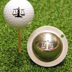 Tin Cup - Lawyer Up - Der Tin Cup ist eine Ball Schablone aus Edelstahl mit dem Design einer Waage. Mit einem feinen und wasserfesten Stift laesst sich dann das Design auf den Golf Ball malen.
