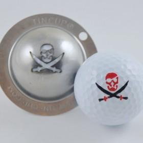 Tin Cup - Fire in the Hole - Der Tin Cup ist eine Ball Schablone aus Edelstahl mit dem Design einer Piraten Flagge. Mit einem feinen und wasserfesten Stift laesst sich dann das Design auf den Golf Ball malen.