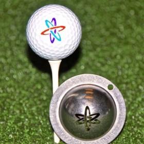 Tin Cup - Nuke It - Dieser Tin Cup ist eine Ball Schablone aus Edelstahl mit der Darstellung eines Atomes. Mit einem feinen und wasserfesten Stift laesst sich dann das Design auf den Golf Ball malen.