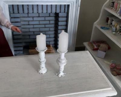 Zwei weiße Kerzenständer mit echten Wachskerzen