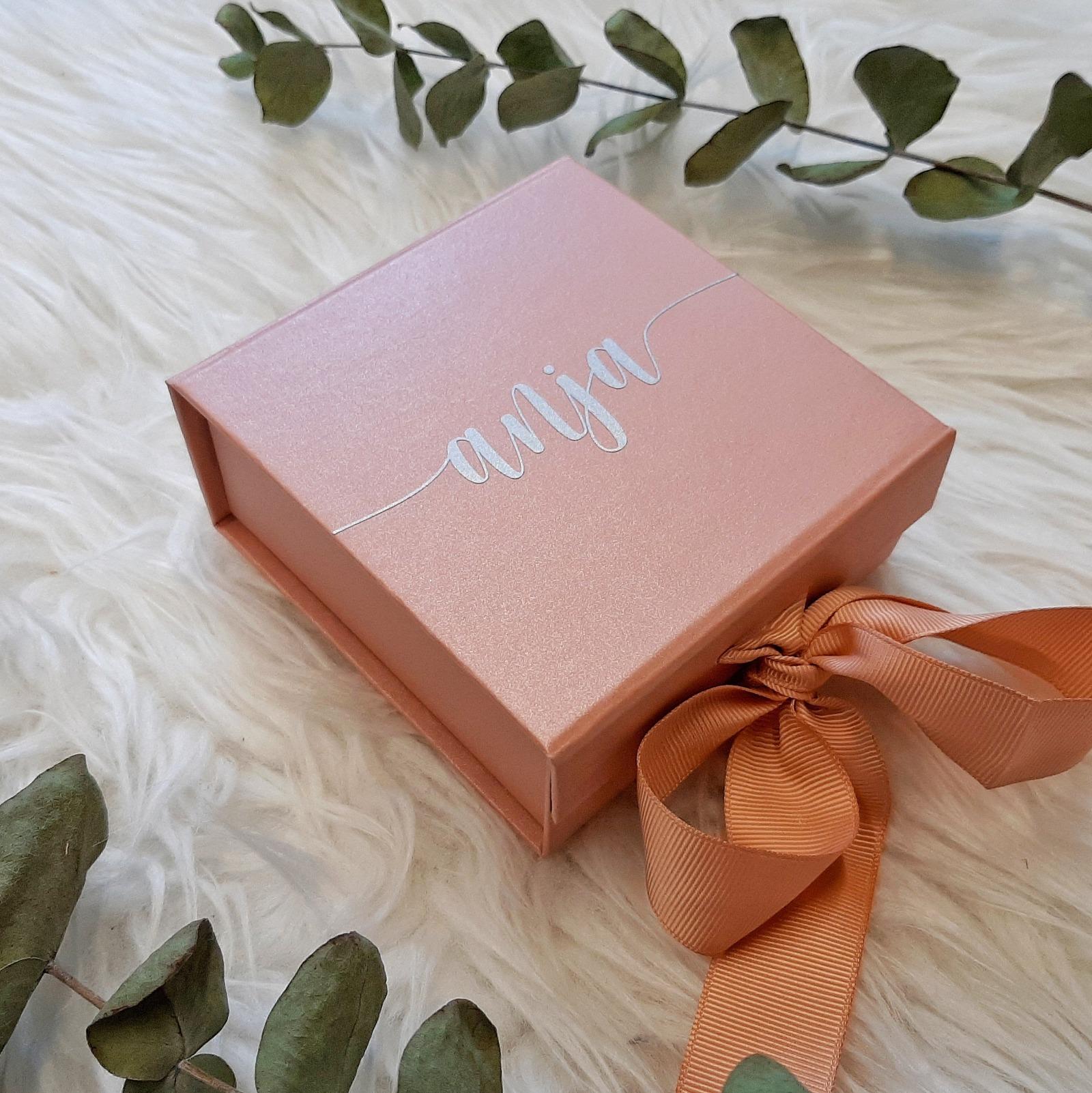 Eine Geschenkbox mit Name und Schleife